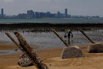 An oyster farmer walks in front of China's Xiamen, ahead of the 60th anniversary of Second Taiwan Straits Crisis against China, on Lieyu island, Kinmen county, Taiwan, 20 August 2018 (Photo: Reuters/Tyrone Siu).